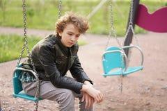 Smutny osamotniony nastolatek plenerowy na boisku szykany adolescencja w komunikacyjnym poj?ciu obraz royalty free