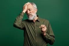 Smutny przygnębiony mężczyzna migrenę, zdejmujący jego macanie i szkła jego czoło zdjęcie royalty free