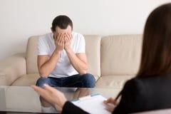 Smutny przygnębiony mężczyzna przy psychologiem, czuć beznadziejnym i desp, Zdjęcie Royalty Free