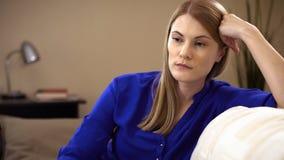 Smutny, przygnębiony młodej kobiety obsiadanie na kanapie, Negatywny emocj i uczuć pojęcie zbiory
