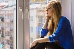 Smutny przygnębiony nastoletni dziewczyny obsiadanie na nadokiennym parapecie zdjęcie stock