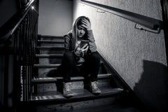 Smutny przygnębiony nieszczęśliwy nastolatek dziewczyny cierpienie od cyberbullying mobilnym mądrze telefonem siedzi samotnie obraz royalty free