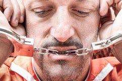 Smutny przygnębiony zatrzymujący mężczyzna z kajdankami w więzieniu Obrazy Royalty Free