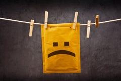 Smutny twarzy emoticon na poczta kopercie zdjęcie stock
