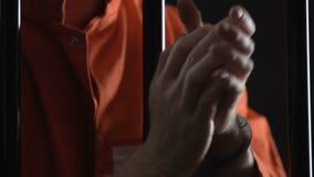 Smutny więzień w kajdankach naciera nadgarstki za komórka barami, zły więzienie uwarunkowywać zbiory