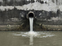 Smutsa ner avrinningen som förorenar en flod Royaltyfri Bild
