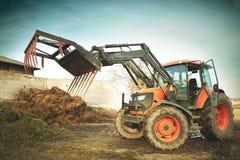 Smutsa ner den jordbruks- traktoren med grasper för dynga som är klar att arbeta Royaltyfri Bild