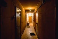 Smutsa ner den tomma mörka korridoren i hyreshus, dörrar som tänder lampor royaltyfri foto