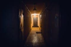 Smutsa ner den tomma mörka korridoren i hyreshus, dörrar som tänder lampor arkivbilder