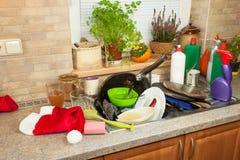 Smutsa ner disk i vasken efter familjberömmar Hem- lokalvård köket Belamrad disk i vasken hushållsarbete Arkivbilder