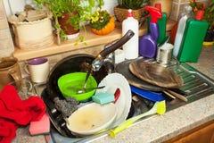 Smutsa ner disk i vasken efter familjberömmar Hem- lokalvård köket Belamrad disk i vasken hushållsarbete Arkivbild