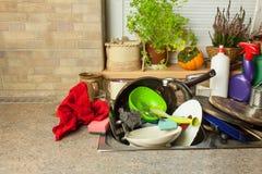 Smutsa ner disk i vasken efter familjberömmar Hem- lokalvård köket Belamrad disk i vasken hushållsarbete Arkivfoton