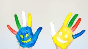 Smutsa ner händer målade olika färger med leenden Begreppet av lycka, det bra lynnet, glädje, kreativitet, konst och målning arkivfilmer