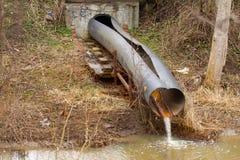 Smutsa ner vatten till floden på industriellt från ett rör Arkivbild