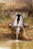 Smutsa ner vatten till floden på industriellt från ett rör Arkivfoto