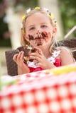Smutsig flicka som äter chokladcaken Royaltyfri Foto