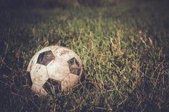 Smutsig fotbollboll på gräs arkivbild
