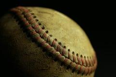 Smutsig gammal baseball med svart bakgrund Arkivbild