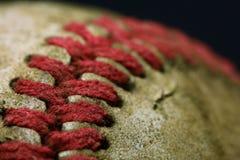 Smutsig gammal baseball på en svart bakgrund arkivfoton