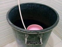 Smutsig gammal svart plast- hink av vatten i badrum royaltyfri foto
