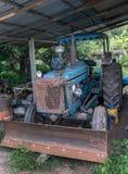 Smutsig gammal traktor som parkeras under ett skjul Arkivfoto