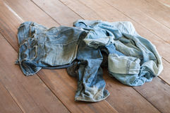 Smutsig jeans på golv Royaltyfri Foto