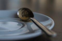 Smutsig kaffesked på en platta Royaltyfri Foto