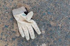 Smutsig kasserad sporthandske på jordningen Fotografering för Bildbyråer