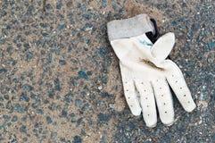 Smutsig kasserad sporthandske på jordningen Arkivfoto