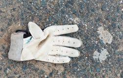Smutsig kasserad sporthandske på jordningen Royaltyfri Bild