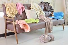 Smutsig kläder spridde på en soffa i rum arkivbild