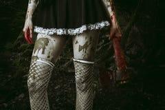 Smutsig kvinnas hand som rymmer en blodig yxa Fotografering för Bildbyråer