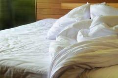 Smutsig ogjord säng med rynkiga ark Arkivbilder
