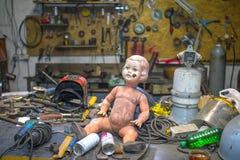 Smutsig plast- behandla som ett barn - dockan som poserar insidan av en metall, shoppar royaltyfria bilder