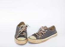 Smutsig sko på vit bakgrund för isolat, övre sko för slut, smutsiga blåttskor på den vita bakgrunden, kanfasblåttskor som är gaml Arkivfoto
