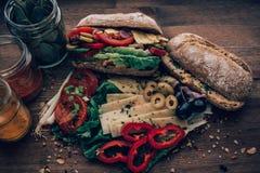 Smutsig smörgås som flödar över med ingredienser royaltyfri fotografi
