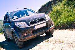 Smutsig SUV på en bergväg Royaltyfri Foto