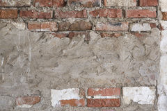 Smutsig tegelstenvägg för Grungy bakgrund med den sjaskiga vita stuckaturen Arkivfoto