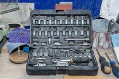 Smutsig uppsättning av hjälpmedel i en ask med skiftnycklar och olika tillbehör för att skruva av på en arbetsbänk efter arbetsda fotografering för bildbyråer