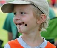 Smutsig vänd mot litet barnpojke för choklad Arkivbild