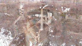 Smutsig vårvattenfall med turister materiel Bästa sikt av den smutsiga vattenfallet som flödar ner skogberget med smältande snö stock video