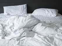 Smutsig vit sängkläderark och kudde i sovrumbakgrund, ogjord smutsig säng efter komfortsömnbegrepp Arkivbild