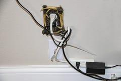 Smutsiga elektriska kablar - för många pluggade in i ett dekorativt elektriskt uttag plus kabel - alla i en tova arkivfoton