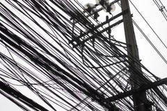 Smutsiga elektriska kablar och trådar på den elektriska polen som isoleras på w Royaltyfri Bild