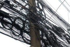 Smutsiga elektriska kablar och trådar på den elektriska polen som isoleras på w Royaltyfri Foto
