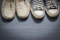 Smutsiga gymnastikskor och skor för vitt läder på kryssfanergrå färggolv arkivbild