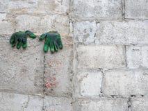 Smutsiga handskar som torkar på betongväggen Arkivbild