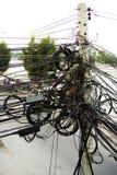 Smutsiga kablar i en konkret stolpe för elektricitet bredvid vägen arkivbild