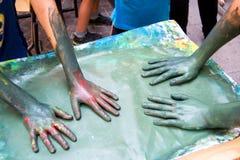 Smutsiga målarehänder på ett smetat målat stycke av papper Royaltyfri Bild