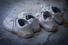 Smutsiga sönderrivna skor Arkivbild